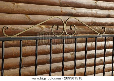 Part Of The Fence Of Black Metal Rods Against A Wooden Brown Wall