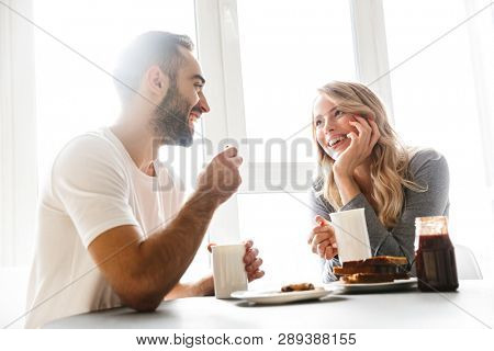 Image of amazing young loving couple sitting at the kitchen have a breakfast talking with each other.
