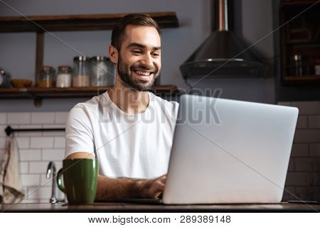 Photo of unshaved man 30s wearing casual t-shirt using silver laptop while sitting at table in modern apartment
