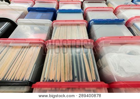 Tall wall of plastic file storage boxes with folders, binders and miscellaneous supplies.