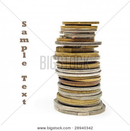 Money - many coins stacked up on a white background with space for text