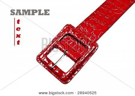 Buckle of a red belt made of artificial animal skin