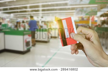 Hand Holding Credit Card And Supermarket Store Abstract Blurred Background, Online Shopping Concept