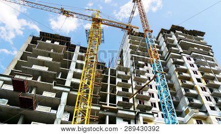 Two Cranes Near Building Under Construction. Skyscraper Construction. Construction Site.