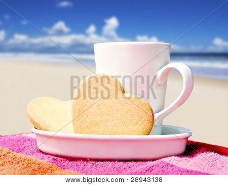 Mug of coffee and heart shaped cookies on a tropical beach