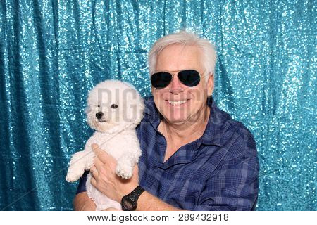 Man with a white dog in a Photo Booth. A Man smiles and poses for photos to be taken in a photo booth.