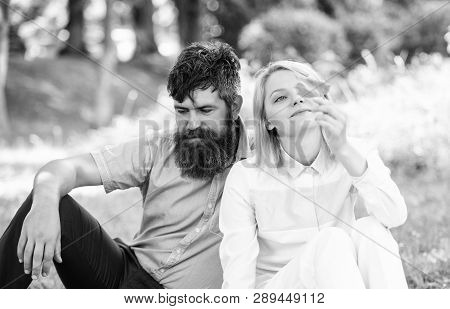 Couple Bearded Man And Woman Enjoy Nature While Sit On Green Grass Meadow. Nature Beauty Concept. Wo