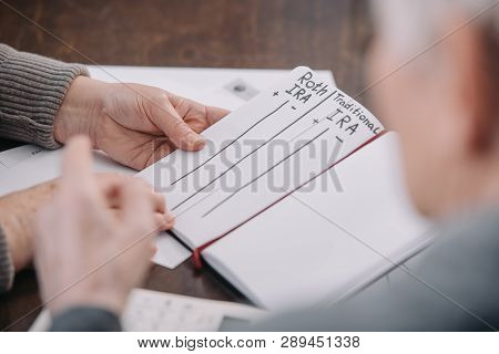 senior couple holding notebook with roth ira and traditional ira words poster