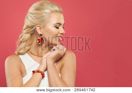 Cheerful Woman In Fashion Golden Bijou Earrings With Red Heart And Coral Bracelet On Pink Background