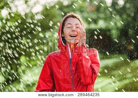 Happy Woman In Red Rain Coat In The Rain