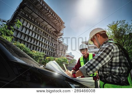 Construction engineers discussion with consultant at construction site or building site of highrise building with blueprints poster