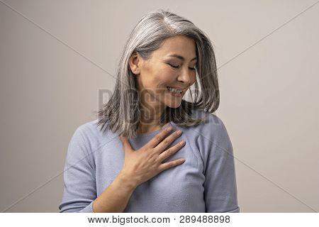 Pleased Middle-aged Asian Woman Touches Her Chest Thanking. Smiling Woman Touching Her Chest With Ha