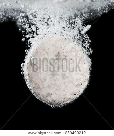 Macro Of Vitamin Tablet Dissolving In Water Against Black Background