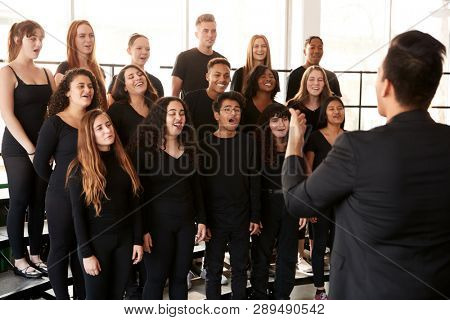 Male And Female Students Singing In Choir With Teacher At Performing Arts School