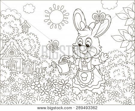 Little Cute Bunny Watering Beautiful Flowers On Its Lawn In Front Of A Small Thatched House On A Sun