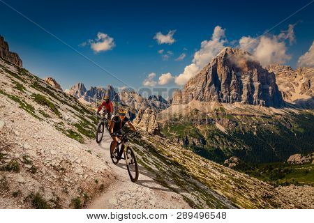 Couple mountain bike rider on electric bike, e-mountainbike rides up mountain trail. Woman and Man riding on e-bike in Dolomites mountains landscape. Cycling trail track. Outdoor sport activity.