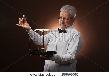 Elderly gray-haired man 50s, in white shirt, glasses and bow tie weighing something on scales with small kettlebells poster