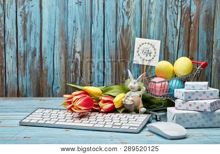 Colored easter eggs in shopping trolley, gift boxes, easter rabbit, tulips flowers  and  computer keyboard and mouse on a wooden  background with copy space. Easter background, Easter shopping.