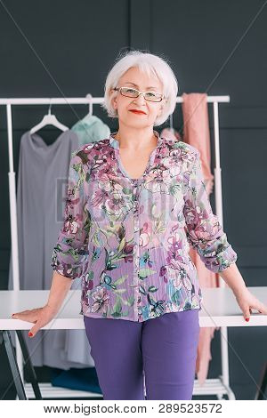Senior Business Woman Workplace. Stylish Fashion Showroom. Content Trendsetter And Coach Looking At