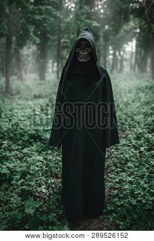Death in black hoodie in forest