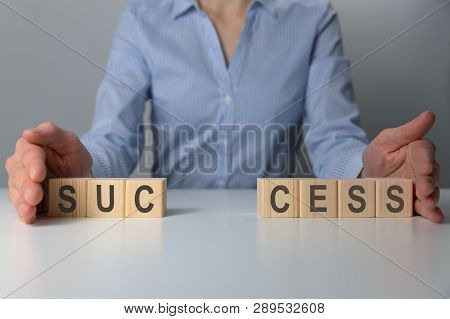 Businesswoman Adjusting 'success' Word Made Of Wooden Blocks. Success Word From Wooden Blocks On Des