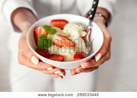 Top View On Girls Hands Holding A Bowl With Vanilla Ice Cream