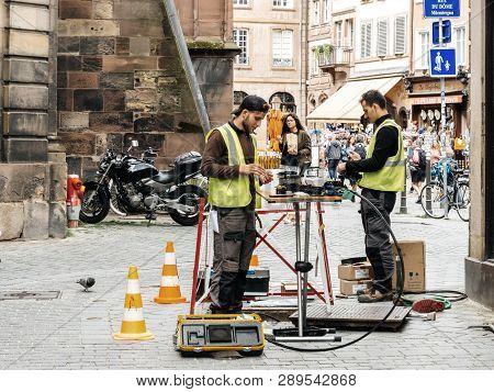 Paris, France - June 13, 2018: Team Working Near Open Sewage Manhole Hole - Internet Provider Compan