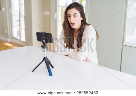 Beautiful young woman recording selfie video with smartphone webcam scared in shock with a surprise face, afraid and excited with fear expression poster