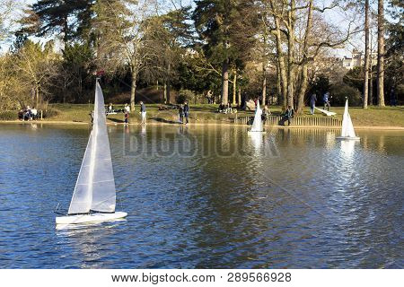 Model Sailboats In A Pond In A Park In Paris. Birds Fly, Parents Walk With Children, Geese In A Pond