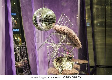 Disco sphere. The scattered chairs and glasses, champagne bottles. Exposition. Decorative show-window. Pink colors. Unusual decision. Chaos. poster
