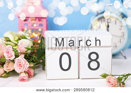 Calendar,  Pink Rose, Pink Candleholder With Fairy Lights, Blue Clock On White Fur Background Agains