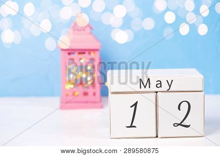 Calendar, Pink Candleholder With Fairy Lights On White Fur Background Against Blue Wall. Selective F