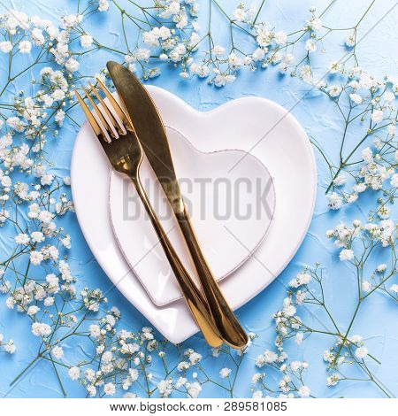 Plates In Form Of Hearts, Golden Knife And Fork And  Fresh White Gypsofila  Flowers On Blue Textured