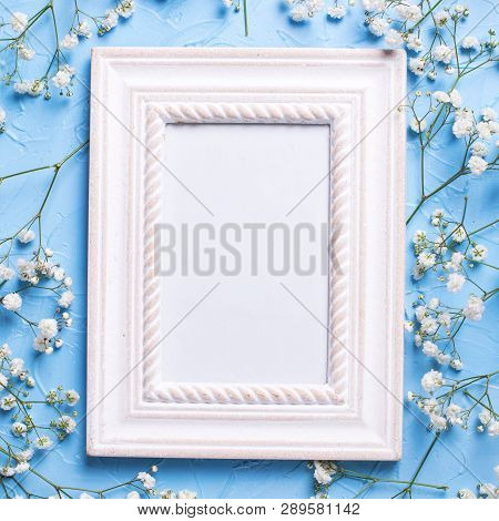 Empty Frame And  Fresh White Gypsofila  Flowers On Blue Textured Background. Top View. Flat Lay. Pla