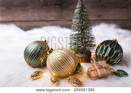 Decorative Fir Tree,  Golden And Green Balls, Boxes With Presents And Fairy Lights On White Fur Back
