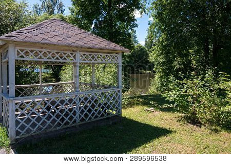 Wooden Summerhouse Standing On Lawn Among Lush Green Trees In Front Of River On Sunny Summer Day
