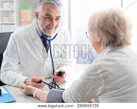 Professional Doctor Measuring A Patient's Blood Pressure
