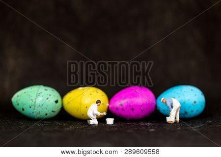 Miniature People  Painting Easter-eggs For Easter Day On Black Background