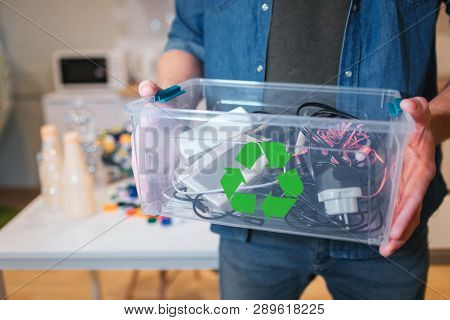 Recycling Concept. An Electronic Waste In Recycling Contaner Close-up. Responsible Man Is Protecting