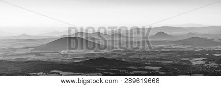 Silhouettes Of Volcanic Hills Of Ceske Stredohori, Central Bohemian Uplands, On Sunny And Hazy Day.