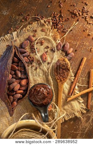 Cocoa Pod ,beans And Cocoa Nibs Setup On Rustic Wooden Background.