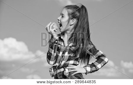 Kid Girl With Long Hair Eat Apple Blue Sky Background. Healthy Nutrition Concept. Child Eat Ripe App