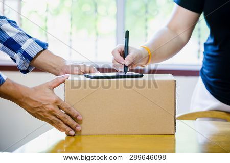 Woman Appending Signature Sign On Smartphone For Sending Boxes With Post Man In Post Office