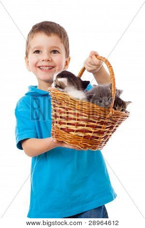 Smiling boy picks up a basket with kittens