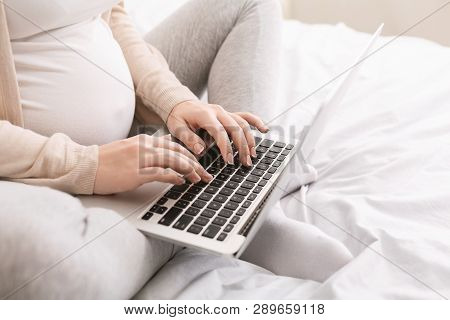 Pregnant Lady Using Laptop, Working In Homeoffice Or Taking Online Education Courses During Maternit