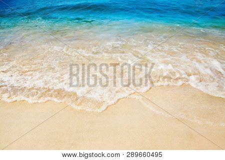 Sandy beach. Splashing waves on the seashore. Summer.