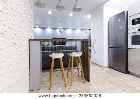 Modern Interior Of Studio Apartment. Bar Counter With Two Bar Chairs In Modern Dining Room.