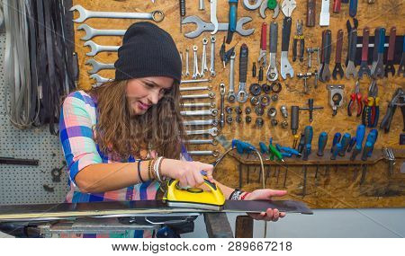 Pretty Girl In Checkered Shirt And Hat Waxing Ski In The Workshop