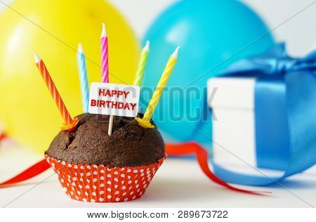 Happy Birthday Party Card With A Chocolate Cupcake, Candles, Gift Box And Colorful Balloons On Backg