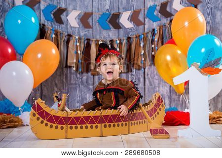 little cute boy in costume of American Indian Apache Chief sits in a canoe. Childrens holiday, happy Birthday 1 year, photo zone decoration poster